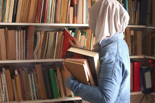 Asian muslim woman wearing hijab picking book in bookshelf, education concept, r Fototapet