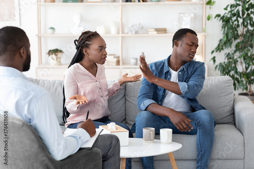 Tela Black couple arguing in front of their therapist at session in office