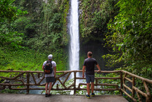 Two Tourists Looking At The La Fortuna Waterfall In Costa Rica