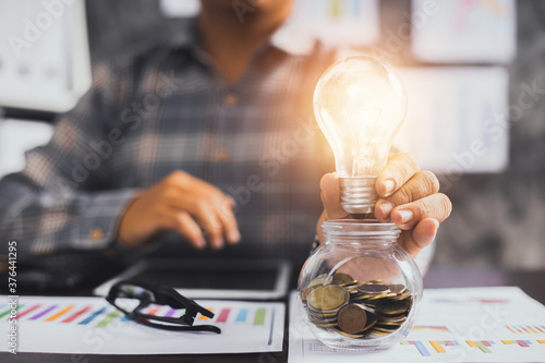 Cuadros en Lienzo Innovation and creative business, businessman holding light bulb on glass of coi