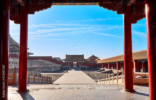 Tela view through an ancient red gate with gold decorations to the square with historical buildings