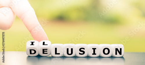 Fotografie, Obraz Hand turns dice and changes the word delusion to illusion.