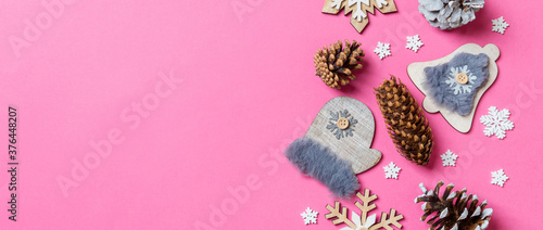 Top view of Banner holiday toys and decorations on pink Christmas background. New Year time concept with copy space