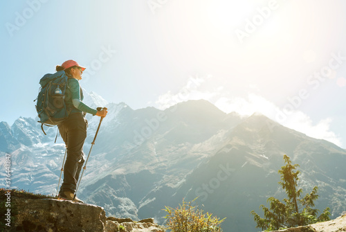 Young hiker backpacker female using trekking poles enjoying mountain view during high altitude Acclimatization walk Fototapet