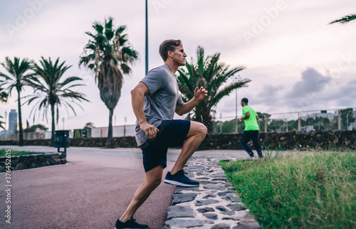 Strong male jogger in activewear doing steps and breathing on cardio training sp Canvas