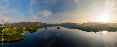 Canvas Print Aerial panorama of sunset next to a beautiful, flat calm lake surrounded by hill