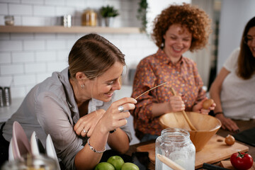 Girlfriends having fun in kitchen. Young women preparing delicious food at home.