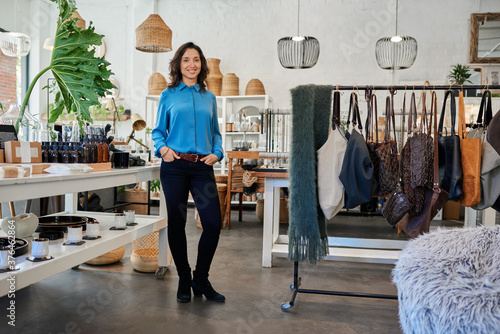 Smiling young Asian entrepreneur standing in her trendy store