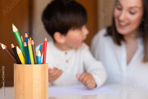 Fotografia Preschooler kid drawing with coloured pencils with mother or teacher educator
