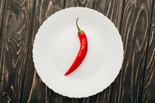 Top View Of Red Chili Pepper On White Plate On Wooden Surface