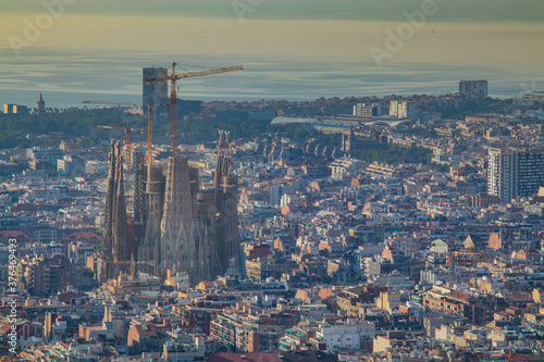 Obraz na plátně Picture of Sagrada Familia, church in Barcelona, surrounded by multitude of other buildings on a sunny summer morning