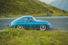GROSSGLOCKNER, AUSTRIA, 17. AUGUST 2018: A Vintage Porsche 356 Sports Car In Blue Color And Whitewall Tires Is Racing Downhill Over The Pass Of Grossglockner In Early Morning.