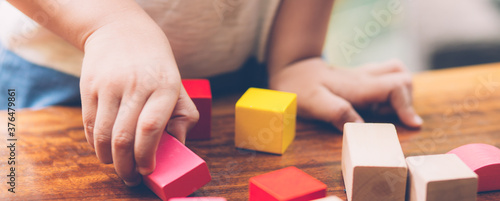 Fotografia, Obraz Closeup hand of boy playing wooden block toy on table for creative with enjoy, happy child learn skill for activity puzzle and creativity for game on desk at home, education concept, banner website