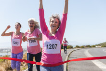Group Of Woman Running Towards The Finish Line Ribbon