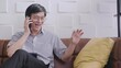 Lifestyle middle-aged Asian man sitting in a living room using a mobile phone call the help center about credit card issues forget passwords credit card usage limits