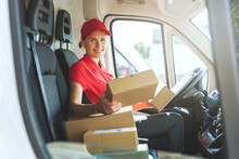 Female Delivery Service Worker In Red Uniform Sitting In Van With Boxes. Smiling At Camera