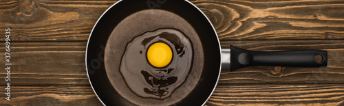 top view of fresh smashed chicken egg in frying pan on wooden surface, panoramic Canvas