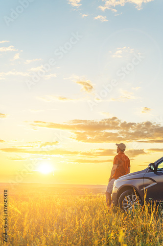A young man in a shirt enjoys the sunset. A man and his car in a field against the backdrop of a brightly lit sunset sky. Local travel concept. Vertical orientation, space for text.