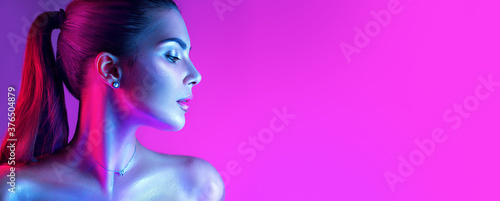 Colorful portrait of a beautiful young woman over purple background. High Fashion model girl in colorful bright neon lights posing in studio, night club. Portrait of beautiful girl in UV. Art design - 376504879