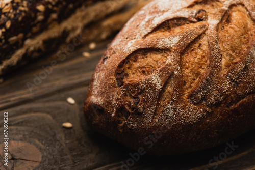 Fototapeta selective focus of fresh baked bread loaf on wooden surface