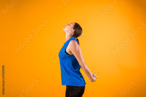 Obraz a beautiful woman in a sports uniform does a neck warm-up on an orange isolated background - fototapety do salonu