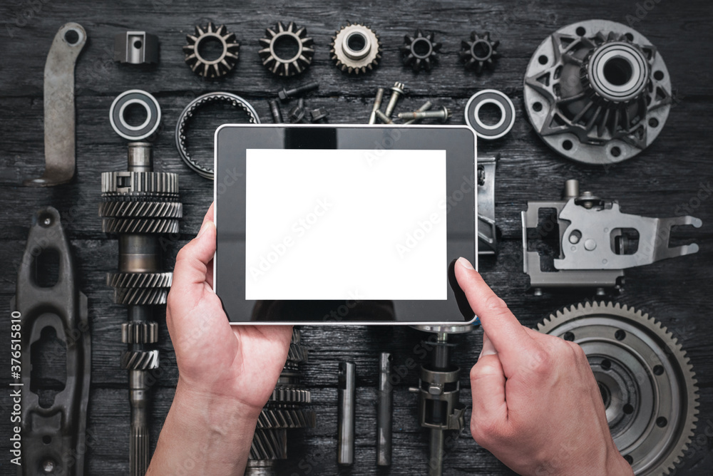 Fototapeta Car service worker is holding a blank screen digital tablet above spare parts background. Car spare parts order online concept.