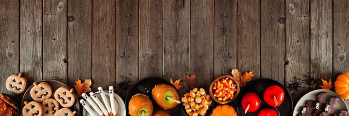 Rustic Halloween treat bottom border over a dark wood banner background with copy space. Above view. Variety of candied apples, cookies, candy and sweets.