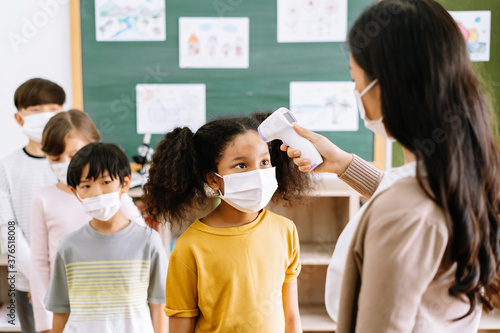 Group of Elementary School Pupils with face mask stood in line let the teacher check, scan thermometer temperature for fever against the spread virus in classroom after covid-19 quarantine Canvas