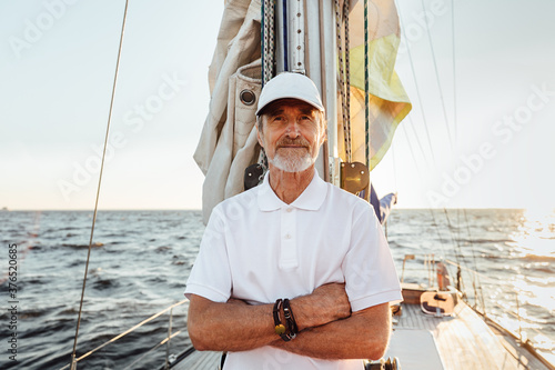 Slika na platnu Portrait of a mature confident captain standing on his yacht at mast and looking