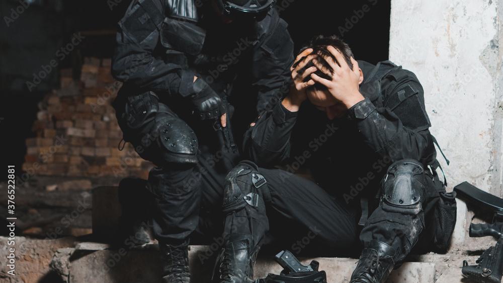 Fototapeta Ranger in black uniform supporting his partner after battle. Help in battle concept.