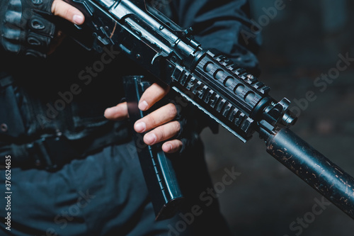 Cuadros en Lienzo Special forces soldier in black uniform reloading the rifle.