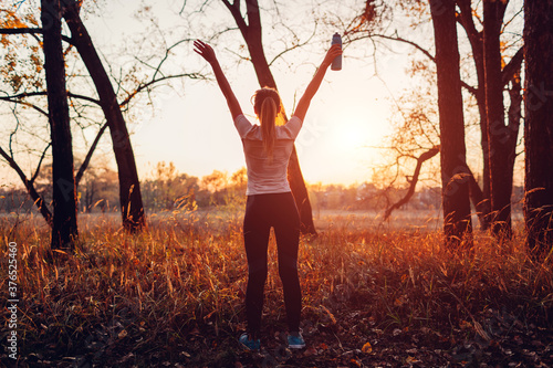 Photo Runner raised arms after workout feeling free and happy succeeded in training