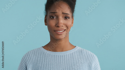 Fototapeta Portrait of confused casual african american girl disappointedly looking in came