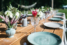 Close Up Of Blue Plates On Wooden Table, Old Fashioned Goblets, Tiny Floral Bouquets On Backyard Wedding Celebration. Jubilee Party Outdoors. Decoration On Table Serving. Concept Of Family Traditions.