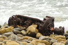 Old Rusty Engine Part On The Beach With The Waves Crashing Into The Rocks At Bluff Cove Beach In Palos Verdes California