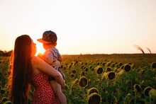 A Young Beautiful Girl With A Baby In Her Arms, In A Red Dress With White Polka Dots Walks In A Sunflower Field. Sunset In The Field.