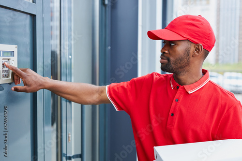 Obraz na plátně afro american man near intercom with orders, worker of delivery service hold foo