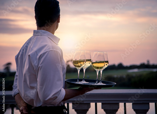 Obraz na plátně Waiter in white shirt holding tray of four wine glasses looking at sunset and go