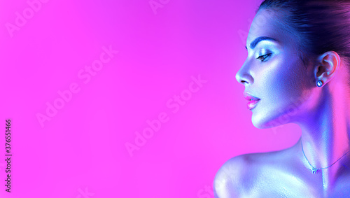 Obraz Colorful portrait of a beautiful young woman over purple background. High Fashion model girl in colorful bright neon lights posing in studio, night club. Portrait of beautiful girl in UV. Art design - fototapety do salonu