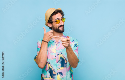 Fotografía young bearded tourist man smiling cheerfully and pointing to camera while making