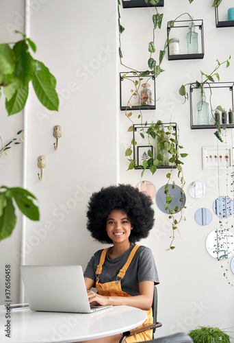 Happy hipster African American young woman with Afro hair using laptop computer in cafe, remote studying, working online, looking at camera sitting in cozy modern coffee shop table, vertical portrait Tableau sur Toile