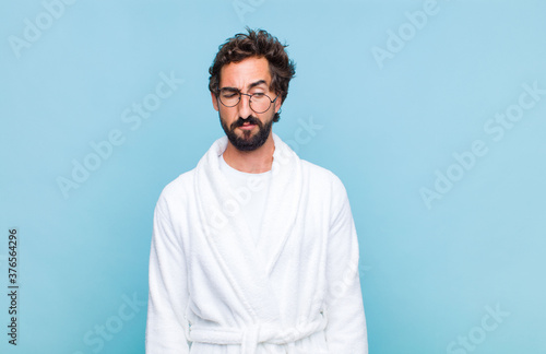 Photo young bearded man wearing a bath robe feeling sad, upset or angry and looking to