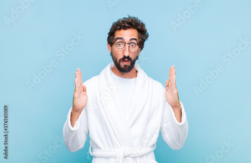 young bearded man wearing a bath robe looking shocked and astonished, with jaw d Billede på lærred