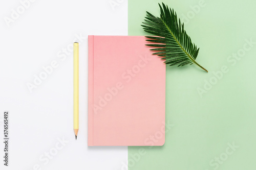 Pink notebook with yellow pencil and palm tree leaf flat lay on white and green paper background. Tropical style composition, top view, copy space.