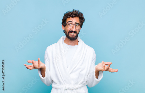 Fotografiet young bearded man wearing a bath robe feeling clueless and confused, not sure wh