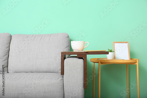 Cup of tea with notebook on armrest table in room Canvas Print