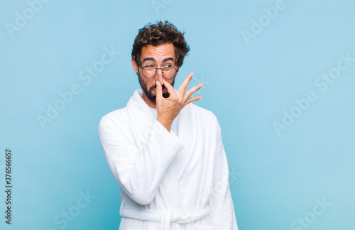 Leinwand Poster young bearded man wearing a bath robe feeling disgusted, holding nose to avoid s
