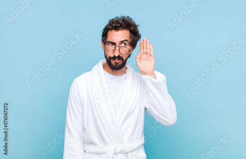 Photo young bearded man wearing a bath robe looking serious and curious, listening, tr