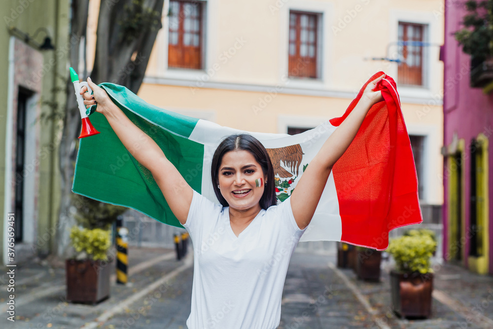 Fototapeta mexican woman at independence day in Mexico holding a flag of mexico
