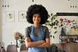 Leinwandbild Motiv Happy African American young woman with Afro hair modern cafe small business owner, female waitress in reopened restaurant looking at camera standing arms crossed in cozy cafe interior. Portrait.